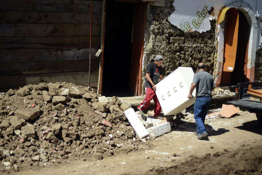 Two men remove furniture from a house damaged by an earthquake in San Marcos, 260 km from Guatemala City, on November 8, 2012. A 7.4-magnitude earthquake rocked southwestern Guatemala on Wednesday, killing 48 people and injuring another 150 while more were missing as homes crumbled.  AFP PHOTO/Johan ORDONEZ Photo: JOHAN ORDONEZ, AFP/Getty Images / AFP