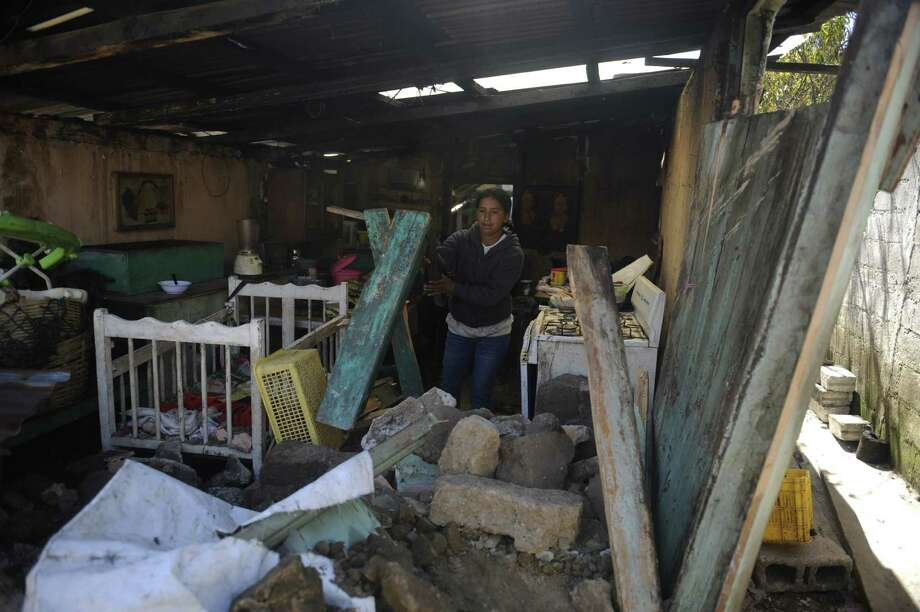 A woman cleans the debris from her home, damaged by an earthquake in San Marcos, 260 km from Guatemala City, on November 8, 2012. A 7.4-magnitude earthquake rocked southwestern Guatemala on Wednesday, killing 48 people and injuring another 150 while more were missing as homes crumbled.  AFP PHOTO/Johan ORDONEZ Photo: JOHAN ORDONEZ, AFP/Getty Images / AFP
