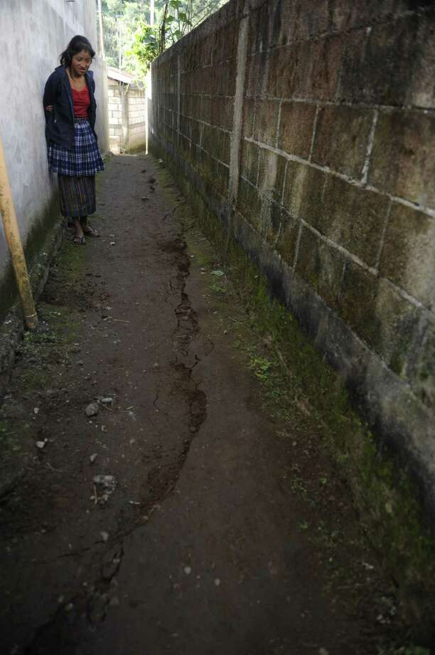 A woman looks at a crack on the ground caused by the evening's earthquake in the San Cristobal Cuchu municipality in San Marcos, 260 km from Guatemala City. A 7.4-magnitude earthquake rocked southwestern Guatemala on Wednesday, killing 48 people and injuring another 150 while more were missing as homes crumbled.     AFP PHOTO/Johan ORDONEZ Photo: JOHAN ORDONEZ, AFP/Getty Images / AFP