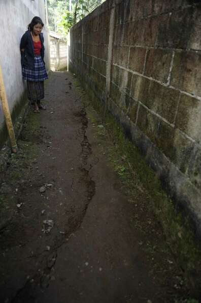 A woman looks at a crack on the ground caused by the evening's earthquake in the San Cristobal Cuchu