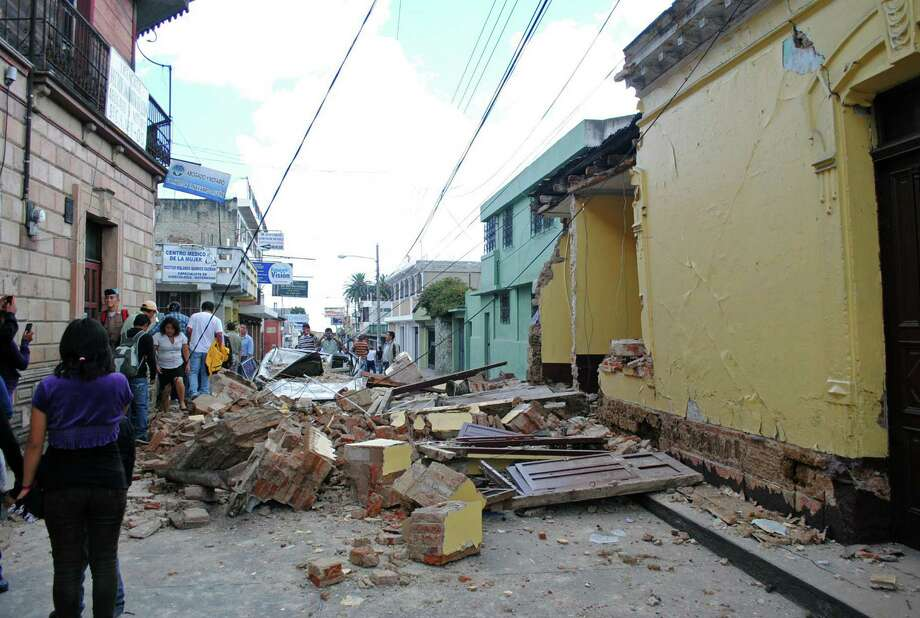 Locals stare at damages in a house in San Marcos, 240 km of Guatemala City, after the city was hit by an earthquake on November 7, 2012. At least 39 people died in southwestern Guatemala after a strong 7.4-magnitude earthquake struck off the country's Pacific coast on Wednesday, Guatemalan President Otto Molina said.   AFP PHOTO Photo: STR., AFP/Getty Images / AFP