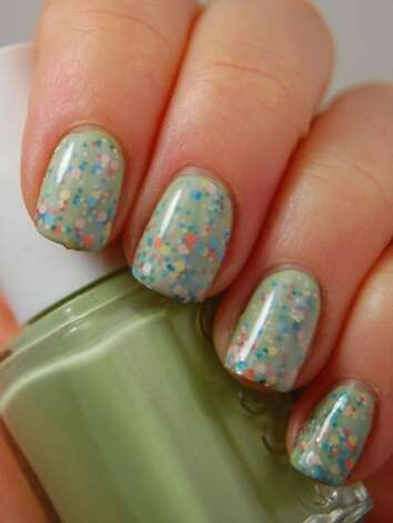 "Confetti nails Start with an opaque, pigmented pastel (pictured here is Essie ""Navigate Her""). Add one layer of a chunky multi-colored glitter (pictured here is Milani ""Gems""). Top with one of two coats of a sheer milky polish (OPI ""So Many Clowns...So Little Time""). This manicure will take a bit longer to dry because of all the layers.  Manicure courtesy of Amy at Gotham Polish.