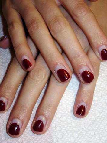 "Reverse French manicure Start by shaping nails carefully (the design is simple, so symmetry and neatness are important). Apply a clear or milky base coat to all ten nails. Using a burgundy or wine polish (try Illamasqua ""Unnatural"") make one stroke down the center of the nail, leaving a gap at the cuticle. Use two more strokes to create an area of polish which mimics the shape of your nail, and leaves a space around the entire cuticle area. Repeat on other nails, and go back with more polish for a second coat to make sure all polished areas are opaque. Allow each nail to dry for two minutes and seal with a top coat, and then apply cuticle oil.  Manicure courtesy of Fleury of Fleury Rose Nails.