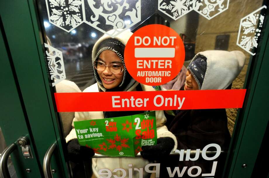 """A Black Friday shopper, who declined to give her name, waits at the front of a line shortly before Target's 5 a.m. opening on Friday, Nov. 27, 2009, in Daly City, Calif. Customers began lining up around 10 p.m. Thanksgiving night for deals that included 40"""" LCD televisions for $449 and 50% off certain items. (Noah Berger / Special to The Chronicle)"""
