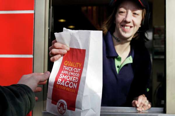 FILE - In this Feb. 28, 2012 file photo a bag of fries is handed to a customer through the drive through window at a Wendy's restaurant in Falmouth, Maine. Wendy's push to remake itself as a higher-end hamburger chain is starting to pay off, with a key sales figure rising for the sixth straight quarter. The company, based in Dublin, Ohio, is trying to pull away from the image of the typical fast-food chain and cast itself as a purveyor of higher-quality burgers and sides. The move reflects the growing popularity of chains such as Chipotle and Panera, which offer better quality food for slightly higher prices. (AP Photo/Pat Wellenbach, File)