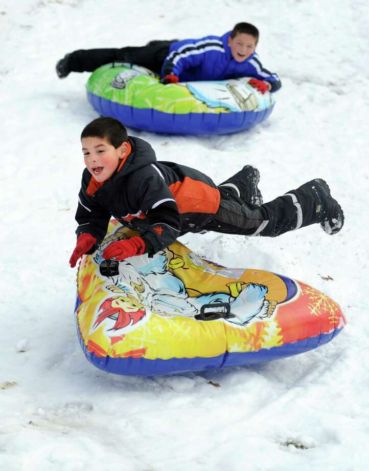Michael Anroman, 7, of Seymour, goes over a bump while sledding behind Derby Middle School Thursday, Nov. 8, 2012 followed by his brother Johnny, 9. Photo: Autumn Driscoll / Connecticut Post