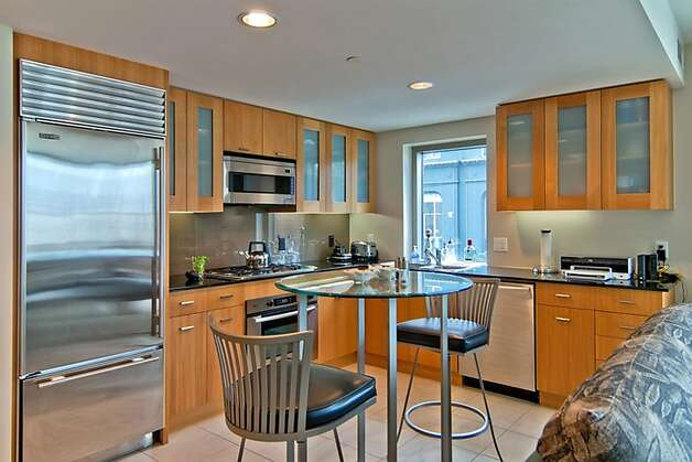 The signature-corner unit's floor plan includes a kitchen featuring stainless steel appliances, glass-front oak cabintery and granite countertops. Photo: Climb Real Estate Group