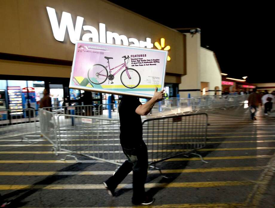 A shopper walks to his car after purchasing a bike at Walmart in Butler Plaza on Thursday, Nov. 24, 2011, in Gainesville, Fla. Walmart opened stores on Thursday. (Associated Press)