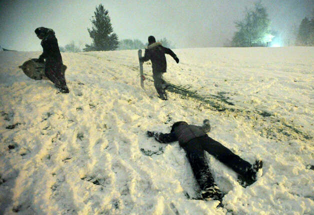 Kai Baldwin, 10, foreground, makes a snow angel, and James Lema, 12, left, and Javen Duff, 11, climb the hill in front of Immaculate High School with their snowboards during the first snowfall of the season. Photo: Jason Rearick / The News-Times