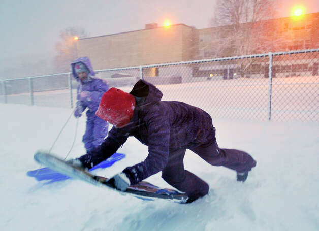 Sophie Rundhaug, 12, foreground, sleds down the hill behind Immaculate High School in Danbury as her sister, Grace, 7, looks on, during the first snowfall of the season. Photo: Jason Rearick / The News-Times