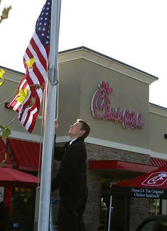 Sam Sbalbi raises the American flag soon after a new Chick-fil-A restaurant opened for business in Walnut Creek, Calif. on Thursday, Nov. 8, 2012, where gay rights activists were on hand to protest the grand opening. Photo: Paul Chinn, The Chronicle