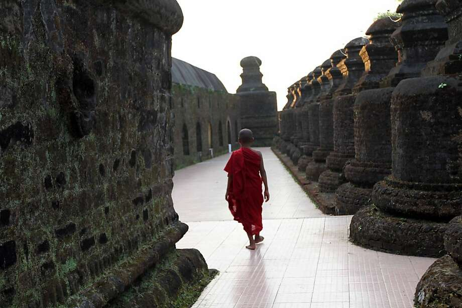A Myanmar Buddhist novice monk walks past ancient pagodas,  in Mrauk U, in Rakhine state, western Myanmar, THursday, Nov. 8, 2012.  (AP Photo/Khin Maung Win) Photo: Khin Maung Win, Associated Press