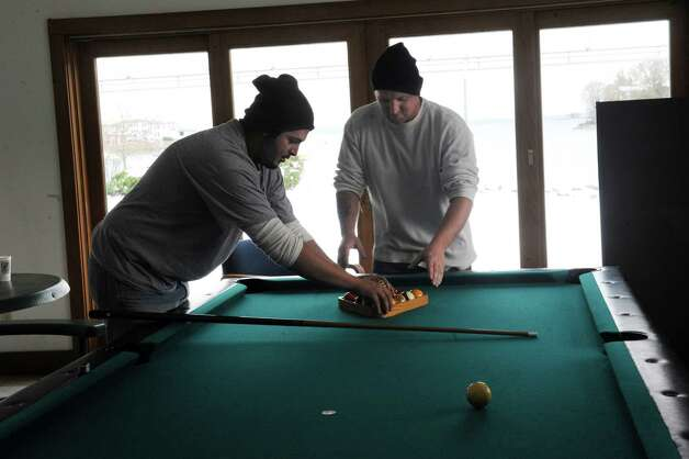 Joe Curtis, left, Greg Gordon, both of Texoma, play pool at the Greenwich Boat and Yact Club, at Grass Island Marine, in Greenwich, Conn. Thursday, Nov. 8, 2012, they are waiting for the next job. Trucks from Texoma Powerline Inc. from Sayre, in OK and Asplundh Tree Expert from East Windsor, parks at Grass Island Marina in Greenwich, Conn. while they work in Greenwich on the damage from hurricane Sandy and the Nor'easter. Photo: Helen Neafsey / Greenwich Time