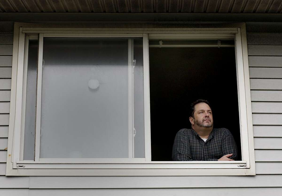 Mark Connors looks out the second floor window of his apartment. He has lived on the island for seven years. Mark Connors, a resident of Treasure Island and neighborhood watch leader, is angry and tired of the routine power outages on the island.