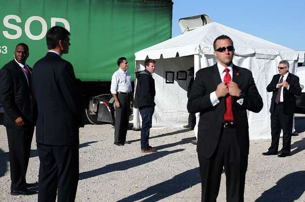 DAVENPORT, IA - OCTOBER 29:  U.S. Secret Service agents surround Republican presidential candidate, former Massachusetts Gov. Mitt Romney (3rd L) and his personal aide Garrett Jackson (R) as they wait backstage before a campaign rally at Seven Cities Sod on October 29, 2012 in Davenport, Iowa. Romney has canceled other campaign events on October 29 and 30 due to Hurrcane Sandy.  (Photo by Justin Sullivan/Getty Images) Photo: Justin Sullivan, Getty Images / 2012 Getty Images