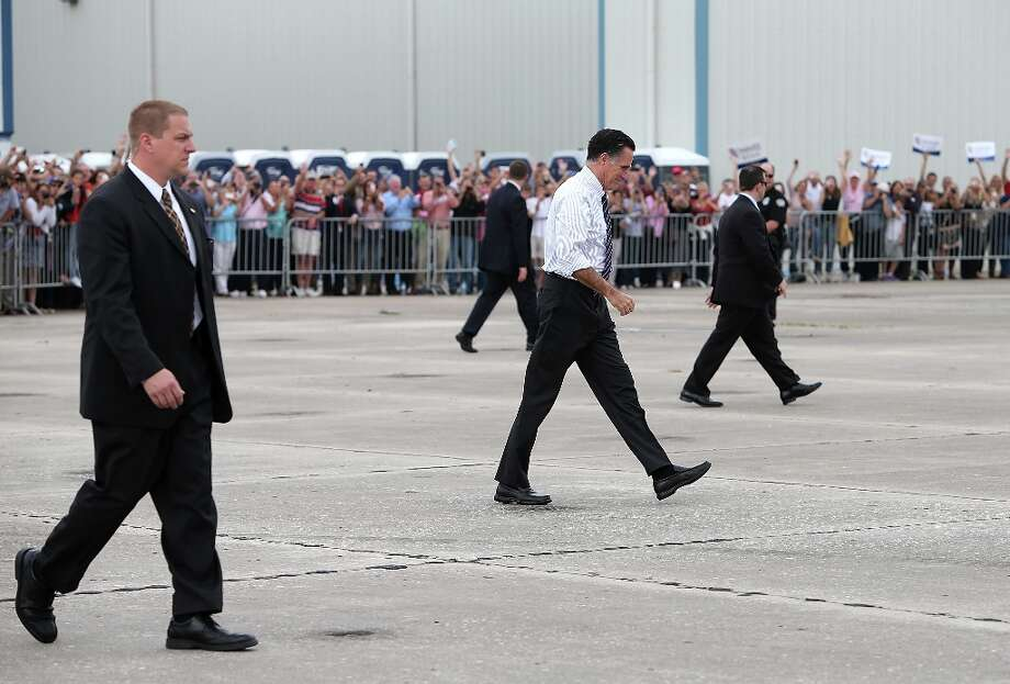 SANFORD, FL - NOVEMBER 05:  Republican presidential candidate, former Massachusetts Gov. Mitt Romney walks with U.S. Secret Service agents as he leaves a campaign rally at Avion Jet Center on November 5, 2012 in Sanford, Florida. With one day to go until election day, Romney is making one final push throughout swing states.  (Photo by Justin Sullivan/Getty Images) Photo: Justin Sullivan, Getty Images / 2012 Getty Images