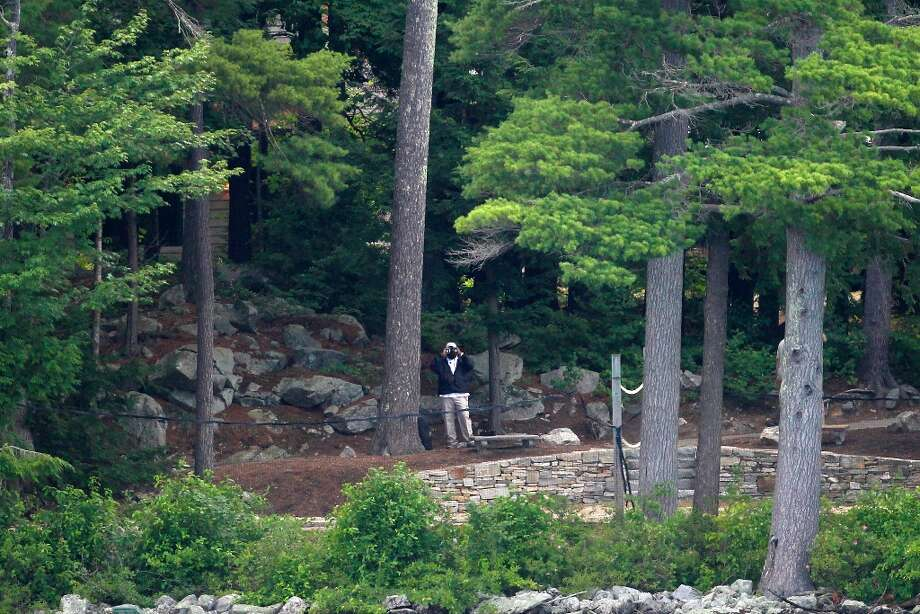 A U.S. Secret Service agent uses binoculars to look out from the vacation home of Republican presidential candidate, former Massachusetts Gov. Mitt Romney on Lake Winnipesaukee in Wolfeboro, N.H., Thursday, July 5, 2012. (AP Photo/Charles Dharapak) Photo: Charles Dharapak, Associated Press / AP