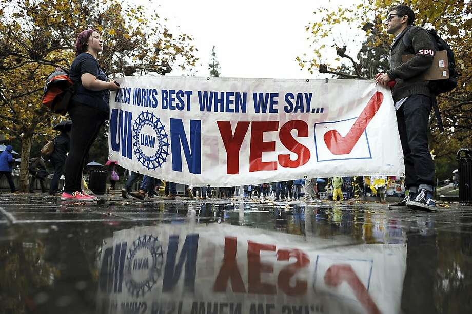 3rd year student Kendal Blum(L) and 4th year student Isaac Kreisman hold a banner as they prepare to lead the crowd to Wheeler Hall to get out of the rain.  Berkeley and other UC campuses staged a walkout to push for using Prop 30 and other funds to immediately roll back tuition and cuts, on the Cal campus in Berkeley, CA, November 8th, 2012. Photo: Michael Short, Special To The Chronicle