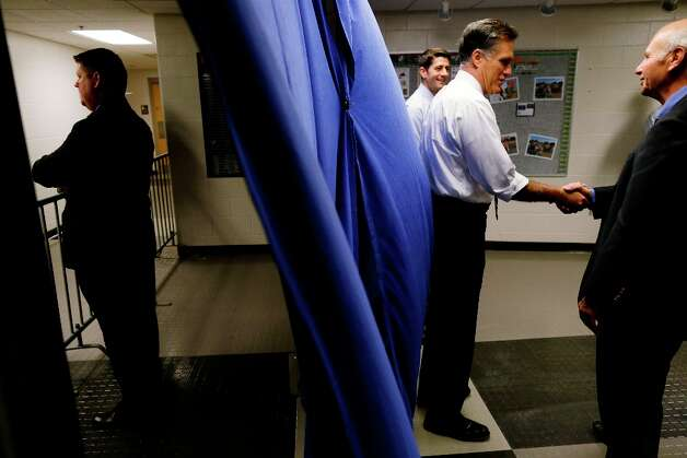 A U.S. Secret Service agent, left, stands watch as Republican presidential candidate and former Massachusetts Gov. Mitt Romney and his vice presidential running mate Rep. Paul Ryan, R-Wis., greet supporters during a photo line backstage before the start of a campaign rally at Koehler Athletic Complex, University of Findlay, Sunday, Oct. 28, 2012, in Findlay, Ohio. (AP Photo/Charles Dharapak) Photo: Charles Dharapak, Associated Press / AP