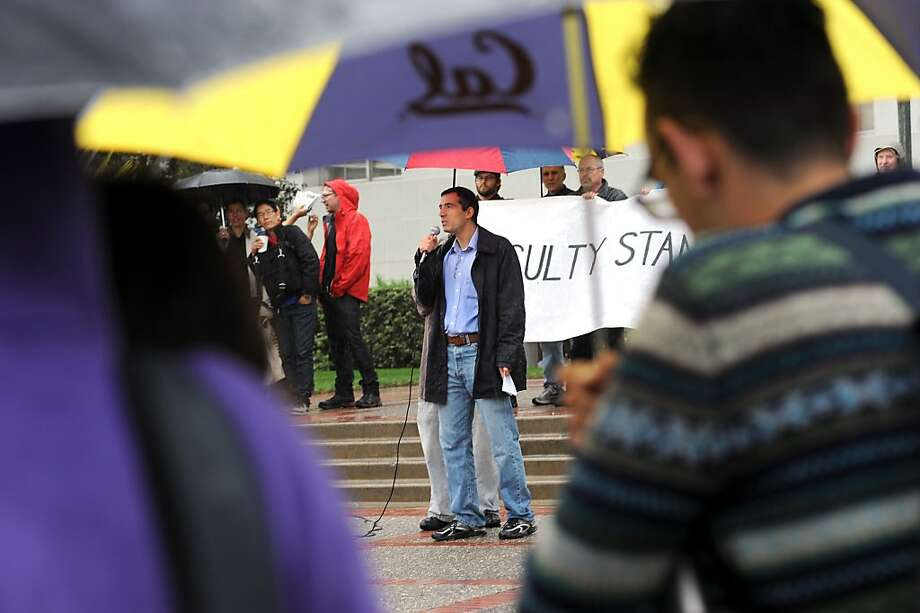 Sociology Professor Cihan Tugal stands under an umbrella as he speaks to the gathered crowd on the steps of Sproul Hall, on the Cal campus in Berkeley, CA.  Berkeley and other UC campuses staged a walkout to push for using Prop 30 and other funds to immediately roll back tuition and cuts, November 8th, 2012. Photo: Michael Short, Special To The Chronicle