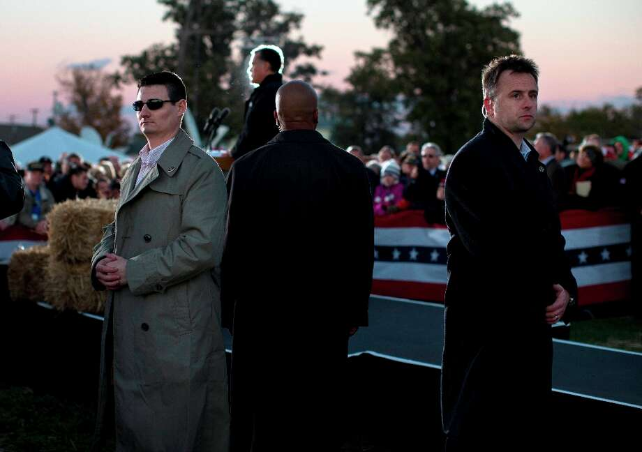 Secret Service agents stand watch as Republican presidential candidate, former Massachusetts Gov. Mitt Romney speaks during a campaign rally at the Shelby County Fairgrounds on Wednesday, Oct. 10, 2012 in Sidney, Ohio.  (AP Photo/ Evan Vucci) Photo: Evan Vucci, Associated Press / AP