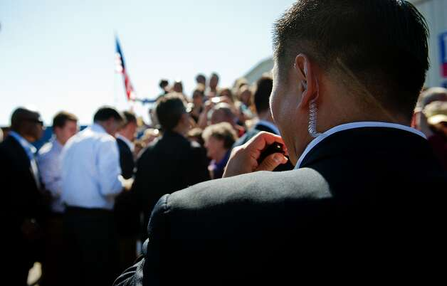 An US Secret Service agent talks into his mouth piece as US Republican presidential candidate Mitt Romney (2nd L) shakes hands with supporters after speaking at a victory rally in Richmond, Virginia, October 12, 2012.                         AFP PHOTO/Jim WATSONJIM WATSON/AFP/GettyImages Photo: JIM WATSON, AFP/Getty Images / AFP