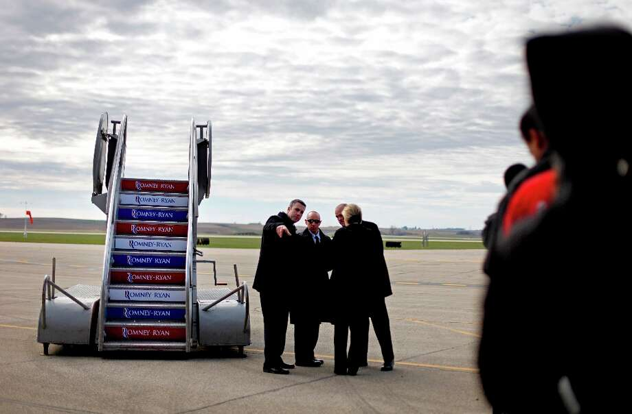 Secret service agents stand next to air stairs as they wait for Republican presidential candidate, former Massachusetts Gov. Mitt Romney to arrive on his plane next to a crowd of supporters, at right, for a campaign event at Dubuque Regional Airport, Saturday, Nov. 3, 2012, in Dubuque, Iowa. (AP Photo/David Goldman) Photo: David Goldman, Associated Press / AP