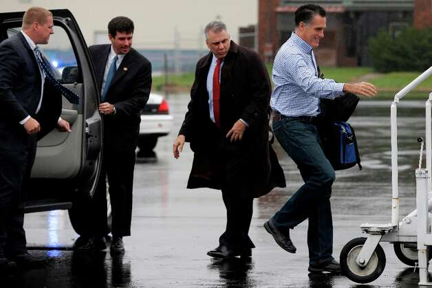 U.S. Secret Service agents watch as Republican presidential candidate, former Massachusetts Gov. Mitt Romney walks in a drizzle to board his campaign plane in Vandalia, Ohio, Tuesday, Oct. 30, 2012, as he travels to Tampa, Fla. for a campaign stop. (AP Photo/Charles Dharapak) Photo: Charles Dharapak, Associated Press / AP