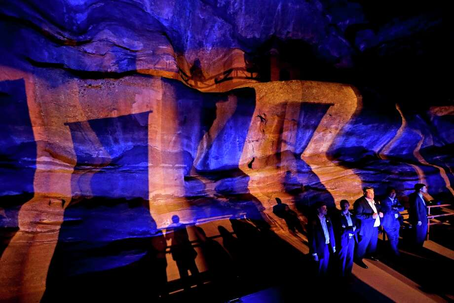 Shadows are cast against a rock wall as secret service agents stand guard behind the stage where Republican presidential candidate, former Massachusetts Gov. Mitt Romney, speaks at a campaign event at the Red Rocks Amphitheatre Tuesday, Oct. 23, 2012, in Golden, Colo. (AP Photo/David Goldman) Photo: David Goldman, Associated Press / AP