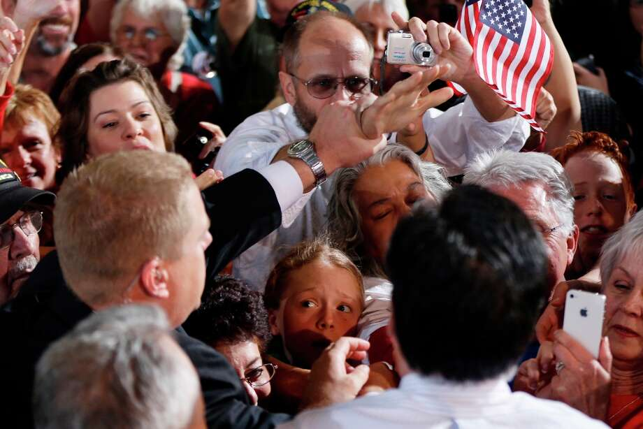 A U.S. Secret Service agent, left, pulls the hand of an unidentified man, background center in white shirt, who would not let go of the hand of Republican presidential candidate and former Massachusetts Gov. Mitt Romney, foreground, as he shakes hands while campaigning at Colorado Springs Municipal Airport in Colorado Springs, Col., Saturday, Nov. 3, 2012. The man was not later detained. (AP Photo/Charles Dharapak) Photo: Charles Dharapak, Associated Press / AP
