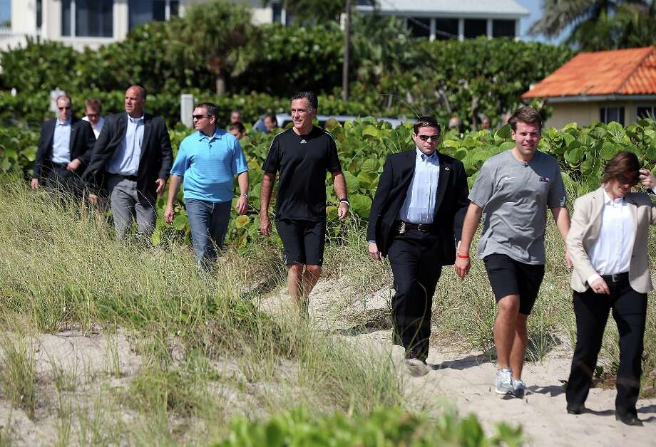 DELRAY BEACH, FL - OCTOBER 21:  Republican presidential candidate, former Massachusetts Gov. Mitt Romney (C) is flanked by U.S. Secret Service agents and staff as he walks to the beach prior to the start of a touch football game on the beach with members of the Romney campaign staff versus some members of the traveling press corps on October 21, 2012 in Delray Beach, Florida. With one day to go before the third and final presidential debate with U.S. President Barack Obama, Mitt Romney is spending the day doing debate prep.  (Photo by Justin Sullivan/Getty Images) Photo: Justin Sullivan, Getty Images / 2012 Getty Images