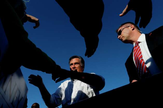 A Secret Service agent, right, watches as Republican presidential candidate and former Massachusetts Gov. Mitt Romney greets supporters as he campaigns at Seven Cities Sod in Davenport, Iowa Monday, Oct. 29, 2012. (AP Photo/Charles Dharapak) Photo: Charles Dharapak, Associated Press / AP