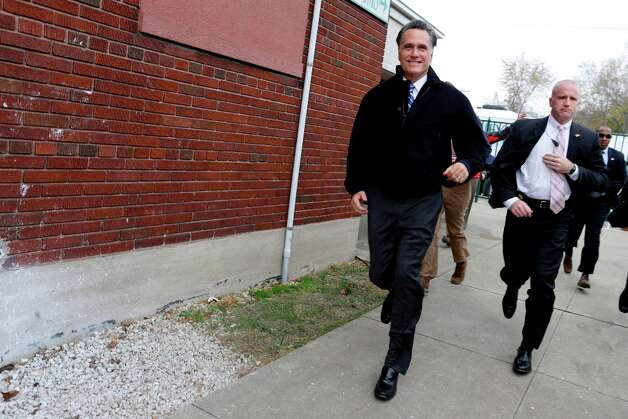 Accompanied by U.S. Secret Service agents, Republican presidential candidate and former Massachusetts Gov. Mitt Romney begins to run towards an overflow crowd gathered outside of Celina Fieldhouse in Celina Ohio. He addressed the audience along with his vice presidential running mate, Rep. Paul Ryan. (AP Photo/Charles Dharapak) Photo: Charles Dharapak, Associated Press / AP