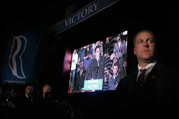 ENGLEWOOD, CO - NOVEMBER 03:  U.S. Secret Service agents keep watch as a video screen displays Republican presidential candidate, former Massachusetts Gov. Mitt Romney speaking during a campaign rally at Comfort Dental Amphitheater on November 3, 2012 in Englewood, Colorado. With less than a week before election day, Mitt Romney is campaigning across the country.  (Photo by Justin Sullivan/Getty Images) Photo: Justin Sullivan, Getty Images / 2012 Getty Images
