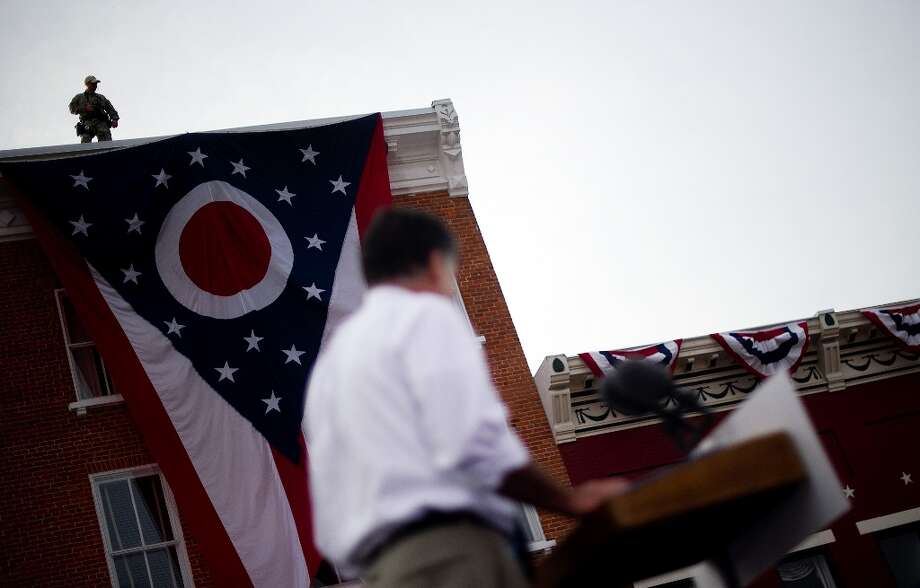 An US Secret Service agent stands lookout from atop a building as US Republican presidential candidate Mitt Romney (C) delivers remarks at a victory rally Lebanon, Ohio, October 13, 2012. As the election draws nearer, the press pool and staff member work around the clock in plain sight, as well as behind the scenes, as US Republican Presidential candidate Mitt Romeny travels across the country to deliver his message.       AFP PHOTO/Jim WATSONJIM WATSON/AFP/GettyImages Photo: JIM WATSON, AFP/Getty Images / AFP