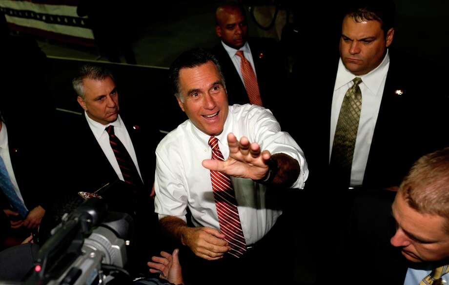 Accompanied by U.S. Secret Service agents, Republican presidential candidate, former Massachusetts Gov. Mitt Romney greets supporters as he campaigns at Integrity Windows in Roanoke, Va., Thursday, Nov. 1, 2012. (AP Photo/Charles Dharapak) Photo: Charles Dharapak, Associated Press / AP