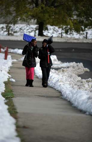 Marquasia Pearson, 14, left, and Kyiana Alston, 13, carry their shovels as they walk up High Street in Ansonia, Conn. Thursday, Nov. 8, 2012. Photo: Autumn Driscoll / Connecticut Post