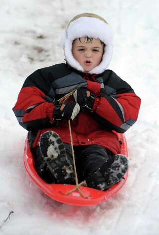 Anton Rusu, 7, of Ansonia, rides his sled down the hill behind Derby Middle School Thursday, Nov. 8, 2012. Photo: Autumn Driscoll / Connecticut Post