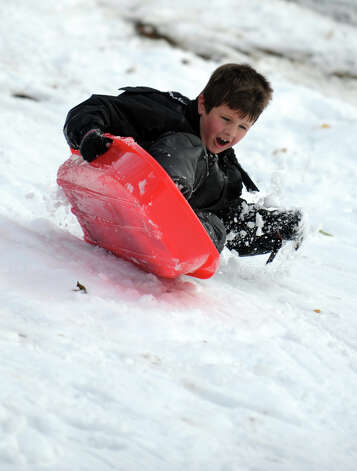 Jake Sobolisky, 7, of Ansonia, rides his sled down the hill behind Derby Middle School Thursday, Nov. 8, 2012. Photo: Autumn Driscoll / Connecticut Post