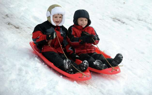 Anton Rusu, 7, of Ansonia, left, and his brother Alex, 5, ride their sleds down the hill behind Derby Middle School Thursday, Nov. 8, 2012. Photo: Autumn Driscoll / Connecticut Post