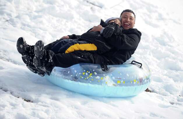 Adrian Garzon and his nephew Raul Flores, 5, of Derby, sled down the hill behind Derby Middle School Thursday, Nov. 8, 2012. Photo: Autumn Driscoll / Connecticut Post
