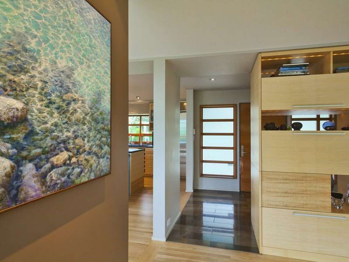 Entry of 1579 34th Court W. The 3,480-square-foot house has three bedrooms, 2.25 bathrooms, vaulted ceilings, big windows, a family room, a den, two fireplaces, central air conditioning, a patio, decks and views of Elliott Bay Marina and the Olympic Mountains on a quarter-acre lot. It's listed for $1.695 million.