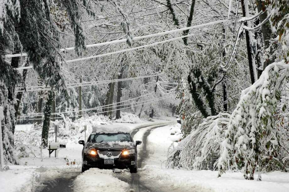 A motorist drives down a snow-covered Ingold Drive after the previous night's nor'easter, in Dix Hills, N.Y., Nov. 8, 2012. Wednesday's snowy nor'easter knocked out power to at least 375,000 homes in New York and New Jersey and interrupted train service on the Long Island Rail Road, setting back the recovery effort in a region still reeling from Hurricane Sandy. (Barton Silverman/The New York Times) Photo: BARTON SILVERMAN / NYTNS