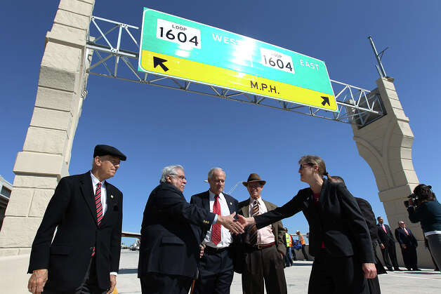 Alamo Regional Mobility Authority Executive Director Terry Brechtel (right) shakes hands with Bexar County Commissioner Paul Elizondo at the unveiling of the new U.S. 281 North to Loop 1604 East and West Direct Connector on Thursday, Nov. 8, 2012. Also in attendance for the unveiling were State Senator Jeff Wentworth (from left), Bexar County Commissioner Tommy Adkisson and Bexar County Judge Nelson Wolff. Construction that began 18 months ago to join the two highways has now been completed and ready to open to traffic. Photo: Kin Man Hui, San Antonio Express-News / © 2012 San Antonio Express-News