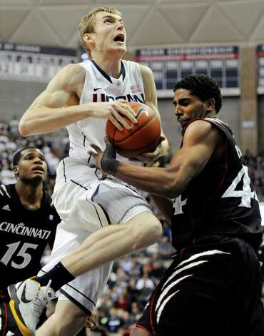 Connecticut's Niels Giffey, left, drives to the basket while Cincinnati's JaQuon Parker, right, defends in the first half of an NCAA college basketball game in Storrs, Conn., Wednesday, Jan. 18, 2012. (AP Photo/Jessica Hill) Photo: Jessica Hill, Associated Press / AP2012