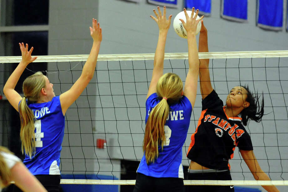 Fairfield Ludlowe's #4 Jennifer Elsaesser, left, and teammate #3 Jaime Quinn, center, reach to block Stamford's #14 Brianna Gordon, during FCIAC Girls' Volleyball Semi-final action in Fairfield, Conn. on Thursday November 8, 2012. Photo: Christian Abraham / Connecticut Post