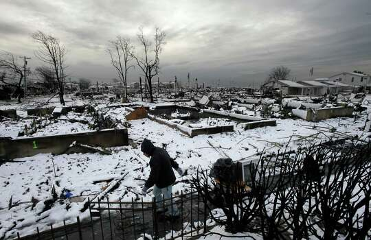 Damon Rasinya carts debris from his family home past the fire-scorched landscape of Breezy Point after a Nor'easter snow, Thursday, Nov. 8, 2012 in New York.  The beachfront neighborhood was devastated during Superstorm Sandy when a fire pushed by the raging winds destroyed many homes. Photo: Mark Lennihan, Associated Press / AP