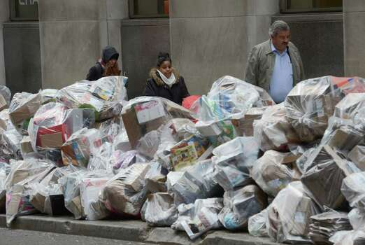 Recyclables piles up on William Street, one block from the New York Stock Exchange, Thursday, Nov. 8, 2012 in New York.  Recycling pickup has been suspended in the wake of Superstorm Sandy. Photo: Henny Ray Abrams, Associated Press / FR151332