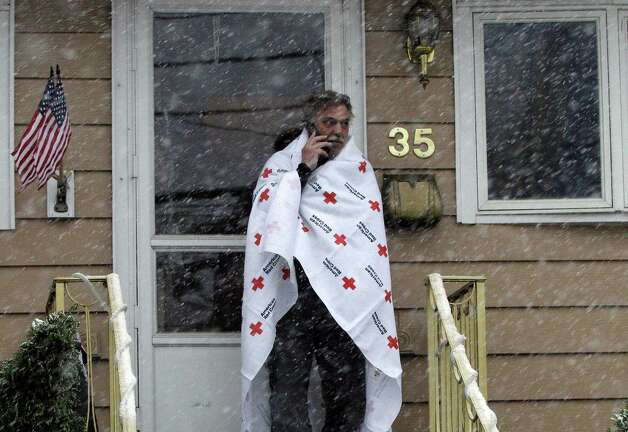 Ben Colontonio talks on his cell phone wrapped in a blanket donated by the American Red Cross as a Nor'easter approaches in the wake of Superstorm Sandy, Wednesday, Nov. 7, 2012, in Little Ferry, N.J. Photo: Kathy Willens, Associated Press / AP