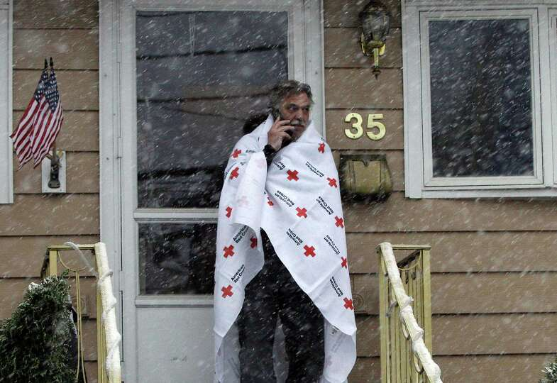 Ben Colontonio talks on his cell phone wrapped in a blanket donated by the American Red Cross as a N